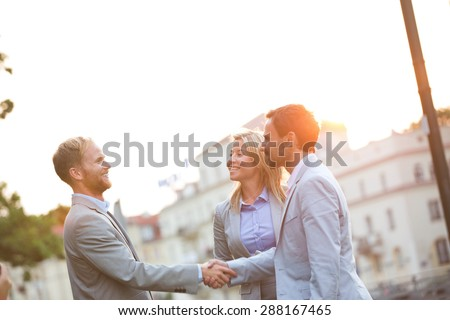 Happy businessmen shaking hands in city against clear sky - stock photo