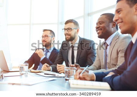Happy businessmen sitting at conference