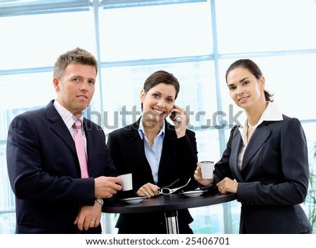 Happy businesspeople having coffee break, smiling. - stock photo