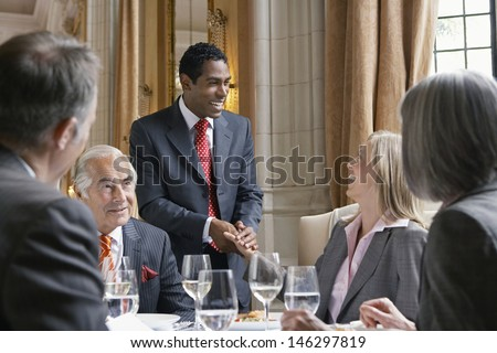 Happy businesspeople in meeting at the restaurant table - stock photo