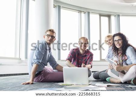 Happy businesspeople looking away while working on floor at creative office - stock photo