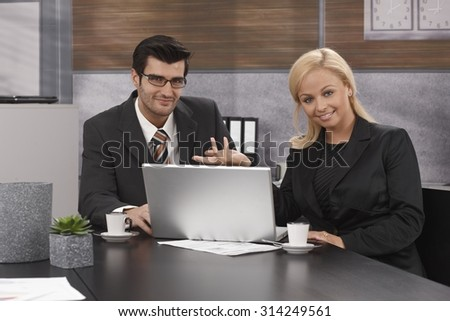 Happy businesspeople sitting at table, working together, using laptop computer, looking at camera. - stock photo