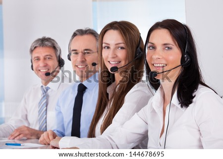 Happy Businesspeople Sitting In A Row With Microphone