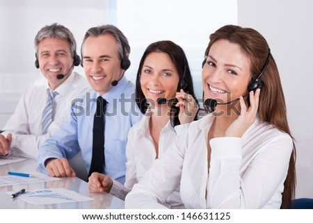 Happy Businesspeople Sitting In A Row With Microphone - stock photo