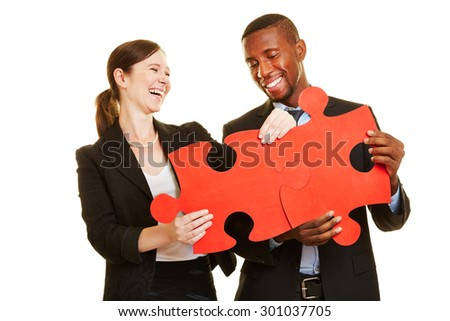 Happy businesspeople solving oversized red jigsaw puzzle together - stock photo