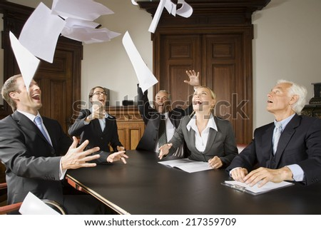 Happy businesspeople throwing papers in the air - stock photo