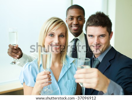 Happy businessteam celebrating a success with champagne in office - stock photo