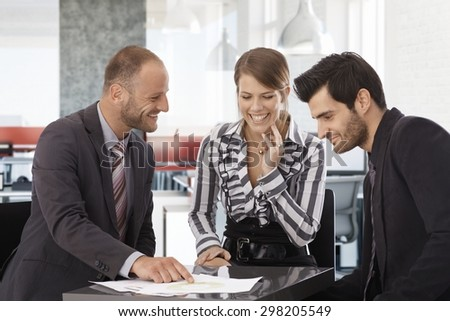 Happy businessteam sitting around table, working together, smiling. - stock photo