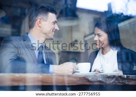 Happy businesswoman and businessman having coffee break in cafe - stock photo