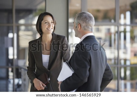 Happy businesswoman and businessman talking in office - stock photo