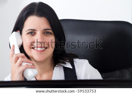 happy businesswoman answering phone in office - stock photo