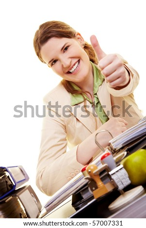 Happy Businesswoman at desk holding her thumb up - stock photo