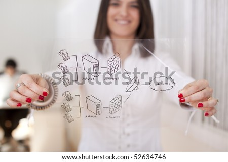 Happy businesswoman at her office showing a firewall schema (selective focus with shallow DOF). - stock photo