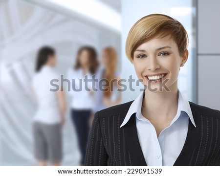 Happy businesswoman at office, colleagues in background. - stock photo