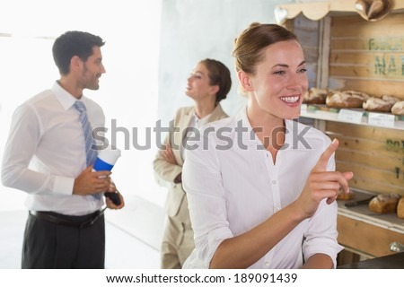 Happy businesswoman at the counter with colleagues behind in office cafeteria