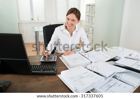 Happy Businesswoman Calculating Financial Data With Calculator At Desk - stock photo