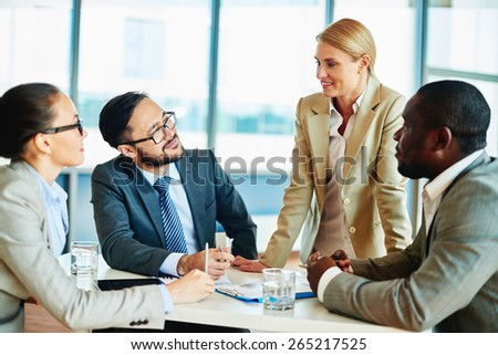 Happy businesswoman explaining her idea to employees at meeting - stock photo