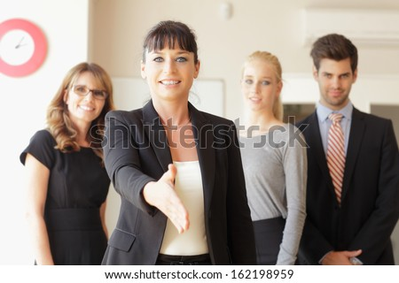 Happy businesswoman going to shake your hand  at office. Her colleagues in the background - stock photo