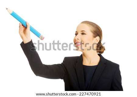 Happy businesswoman holding big pencil