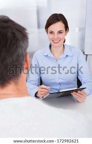 Happy Businesswoman Holding Clipboard With Pen In Front Of Businessman - stock photo