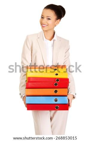 Happy businesswoman holding heavy bidners. - stock photo