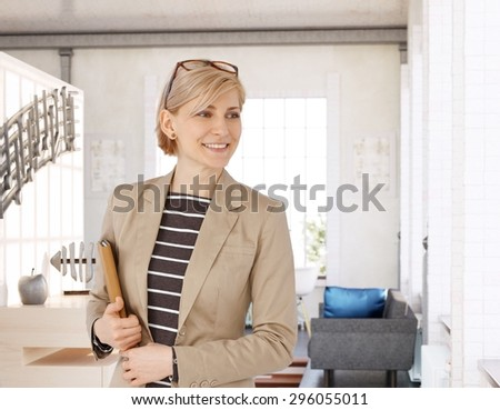 Happy businesswoman holding tablet computer, smiling, looking away. - stock photo