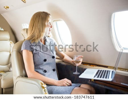 Happy businesswoman holding wineglass while looking through window of private jet - stock photo