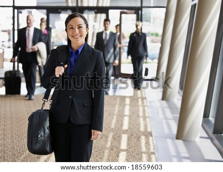 Happy businesswoman in full suit holding briefcase - stock photo