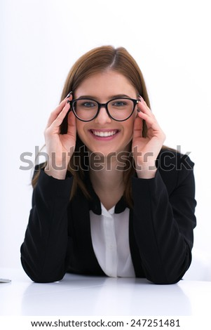 Happy businesswoman in glasses sitting at the table
