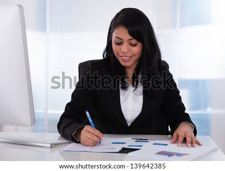 Happy Businesswoman In Office Working On Paper - stock photo