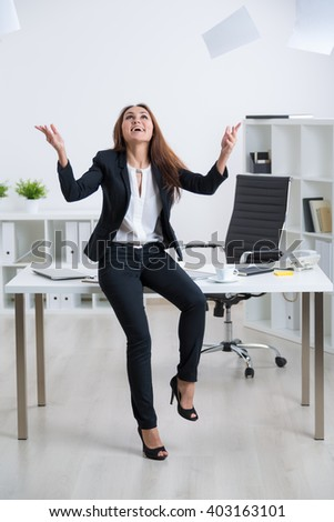 Happy businesswoman in suit sitting on table with hands raised up, paper over her head. Concept of success.