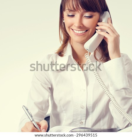 happy businesswoman in white business style clothing or support phone worker - stock photo