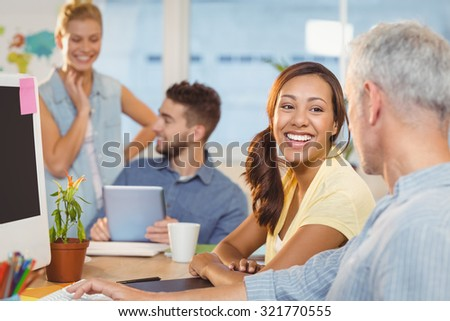 Happy businesswoman interacting with male colleague with employees working in background at creative office - stock photo