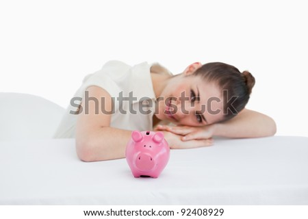 Happy businesswoman leaning on her desk with a piggy bank against a white background - stock photo