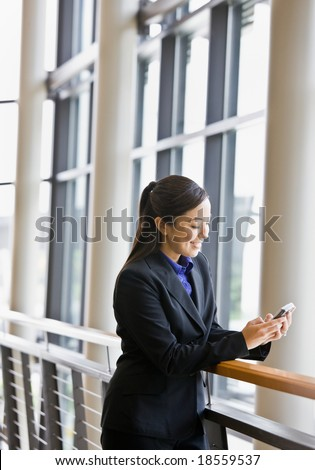 Happy businesswoman leaning on railing in office and text messaging - stock photo
