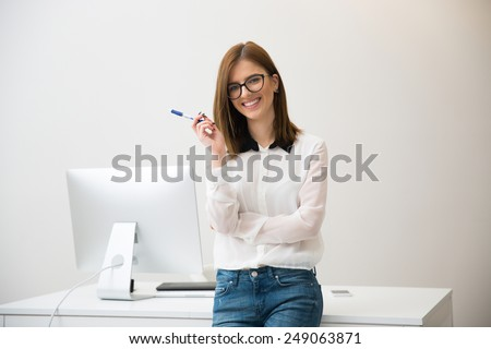 Happy businesswoman leaning on the table in office - stock photo