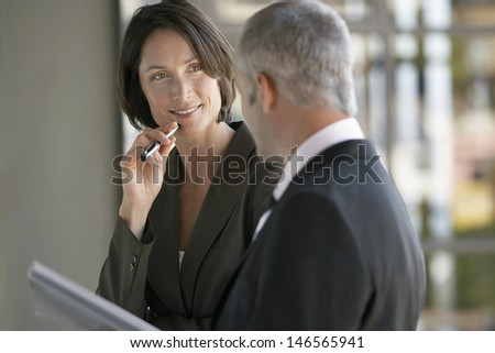 Happy businesswoman listening to male colleague in office - stock photo