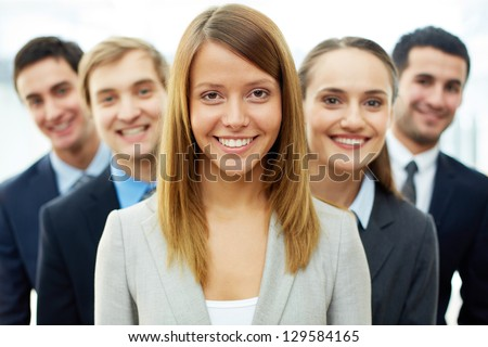 Happy businesswoman looking at camera with smart associates behind - stock photo
