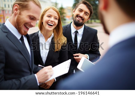 Happy businesswoman looking at colleague while discussing ideas at meeting outside - stock photo