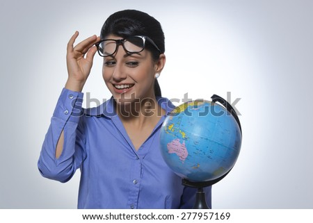 Happy businesswoman looking at globe over glasses against gray background - stock photo
