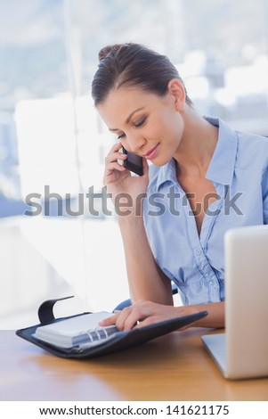 Happy businesswoman looking at her diary and calling in the office