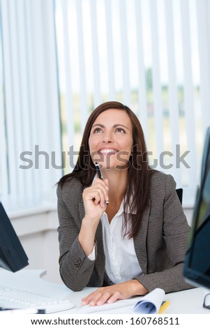 Happy businesswoman looking up with an expression of remembrance sitting at the desk in the office - stock photo