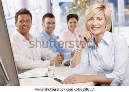 Happy businesswoman on business meeting at office, leaning on table, looking at camera and smiling.