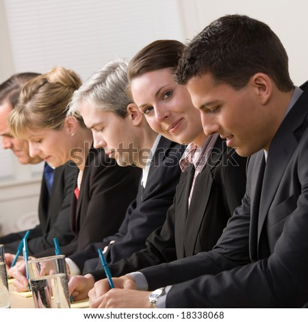 Happy businesswoman on panel of co-workers - stock photo