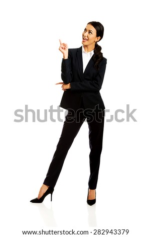 Happy businesswoman pointing at copyspace. - stock photo