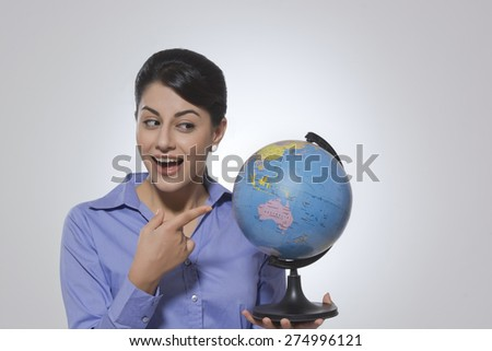 Happy businesswoman pointing at globe against gray background - stock photo