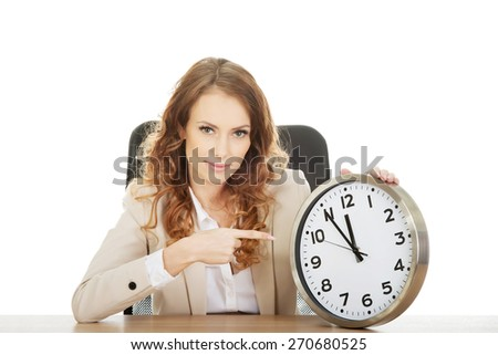 Happy businesswoman pointing on a clock by a desk. - stock photo
