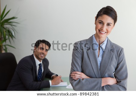 Happy businesswoman posing while her colleague is working in an office - stock photo