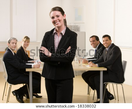 Happy businesswoman posing with co-workers meeting in conference room behind her - stock photo