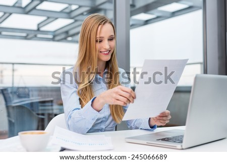 Happy businesswoman reading business report